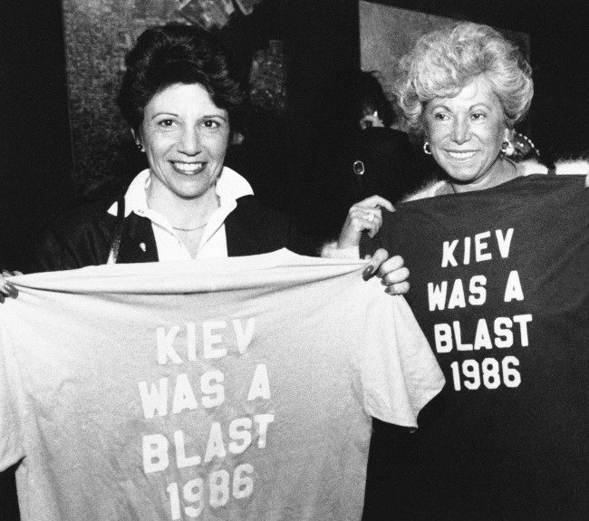 "Marina Pappas, left, and Chrisa Livanos, both mothers of students who returned from Kiev, hold up T-shirts reading ""Kiev Was A Blast 1986"" at Kennedy International Airport in New York, May 3, 1986. Twenty high school students and 11 adults from Long Island, who came within 80 miles of the Soviet nuclear accident, returned home three days early. (AP Photo/Susan Ragan)"
