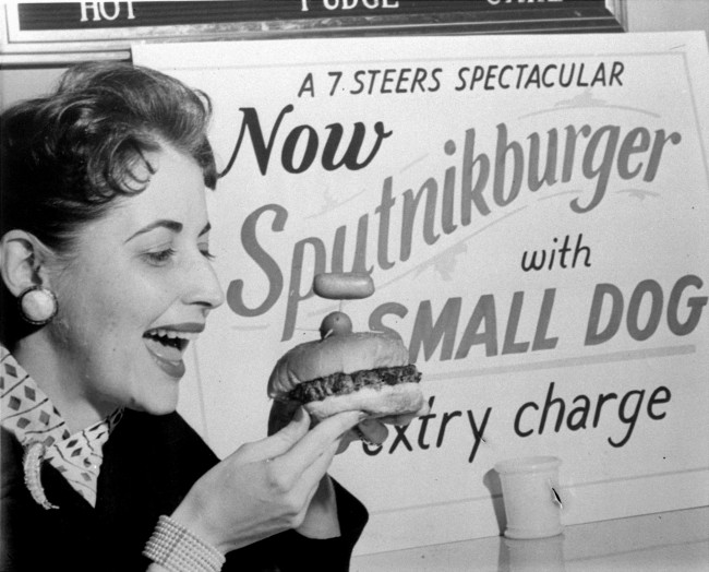 This picture shows an Atlanta, Georgia, restaurant's Sputnikburger, complete with small dog, November 4, 1957. Garnished with Czarist Russian dressing and caviar, the sandwich is topped with a large satellite olive pierced with three toothpicks for antennae. Atop one antenna is a small dog or miniature cocktail hotdog. The sampler is Harriet Phrydas. (AP Photo) Ref #: PA.8690663  Date: 04/11/1957