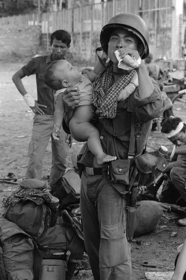 A Cambodian government soldier eats a sandwich and holds his son while waiting to be moved by boat from Phnom Penh on Sept. 9, 1973, to the embattled provincial capital of Kompong Cham. (AP Photo/Billy) Ref #: PA.9217462  Date: 09/09/1973