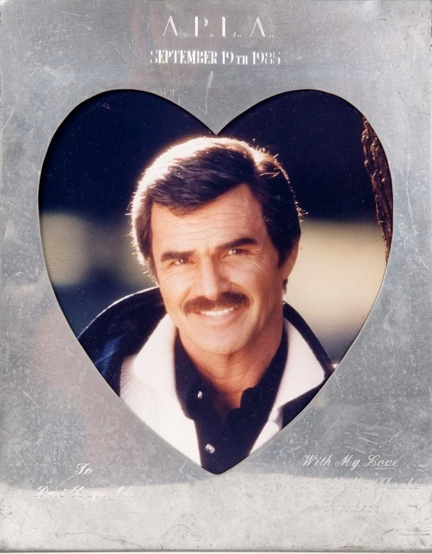 "Estimate: $400 - $600 Starting: $200 A frame with an inscription to Burt Reynolds from Elizabeth Taylor. The silver frame has a heart-shaped window with an image of Reynolds and is inscribed ""A.P.L.A. September 19th 1985 To Burt Reynolds With My Love And All My Thanks Elizabeth."""