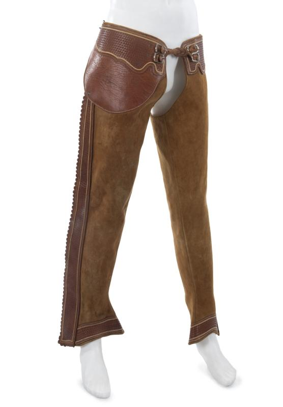 Estimate: $200 - $300 Starting: $100 A pair of Burt Reynolds brown leather chaps. Dark brown trim is tooled to look as though the leather was woven. Additional floral tooling, lacing and buckle closure and faux bone fasteners down the side of each leg.