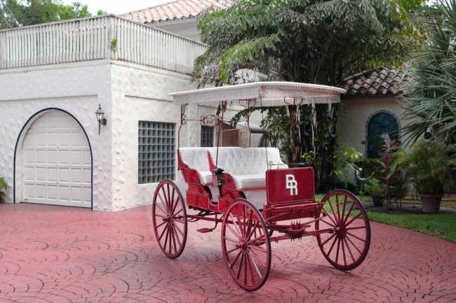 "Starting: $1,500 A custom-built Valley Carriage Works red and white covered carriage with the Burt Reynolds Ranch ""BR"" monogram. This carriage was a gift to Burt Reynolds from Dolly Parton."
