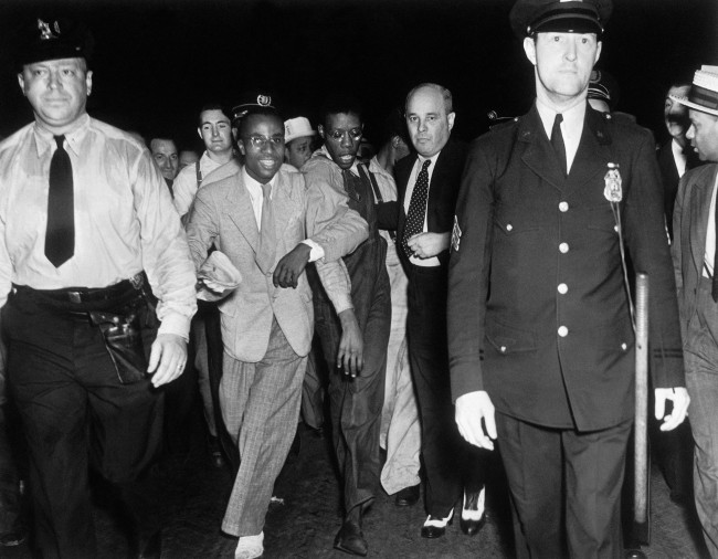 Apparently bewildered by the attention of an uncontrollable crowd, Olen Montgomery is led through Penn Station upon arrival in New York City, July 26, 1937 by his attorney, Sam Liebowitz while an officer marches ahead. (AP Photo). Ref #: PA.13168414  Date: 26/07/1937