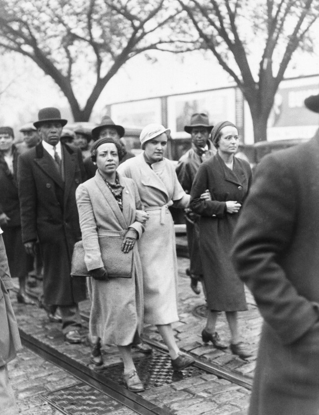 "Ruby Bates, Alabama mill girl who caused a sensation in the last Scottsboro Trial by reversing her previous testimony that she had been assaulted by the Black defendants, leads a parade of several hundred persons through the Washington, D.C. streets to the White house, to present her petition for the liberation of the "" Scottsboro Boys. "" Ruby is the woman in the light coat in the center. ( AP Photo )"