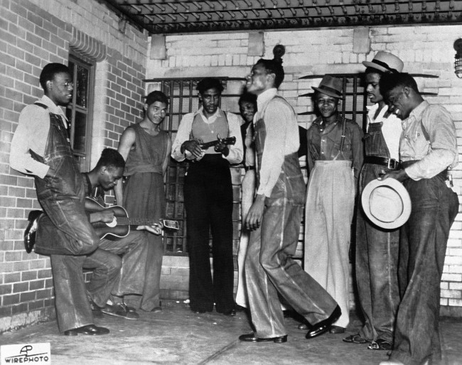 n this July 12, 1937 file photo, the eight men due to be arraigned before the Circuit Court in Decatur, Ala. play music at their jail in Birmingham, Ala. before their court appearance. From left are Olen Montgomery, Andy Wright, Eugene Williams, Charlie Weems, Patterson, Clarence Norris (dancing) Roy Wright, Ozie Powell and Willie Roberson, also known as the Scottsboro Boys. They were convicted by all-white juries of raping two white women on a train in Alabama in 1931. All but the youngest were sentenced to death, even though one of the women recanted her story. All eventually got out of prison, but only one received a pardon before he died. (AP Photo)