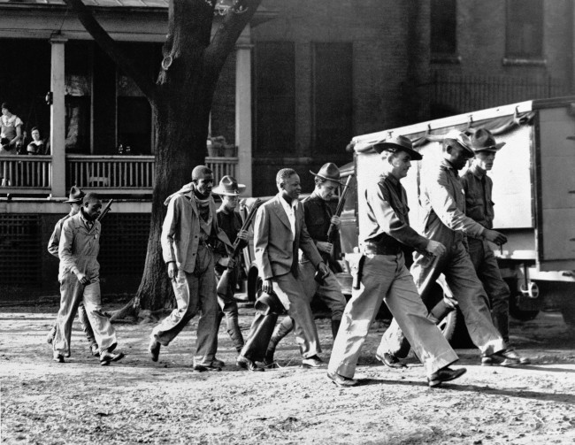 n this April 6, 1933 file photo, four of the Scottsboro Boys prisoners are escorted by heavily-armed guards into the Decatur, Ala., courtroom. Now that the Alabama Legislature is allowing posthumous pardons for the Scottsboro Boys, the nine African-American youths wrongfully convicted of raping two caucasian women more than 80 years ago, there is still much work to be done before their names are officially cleared. (AP Photo/File)