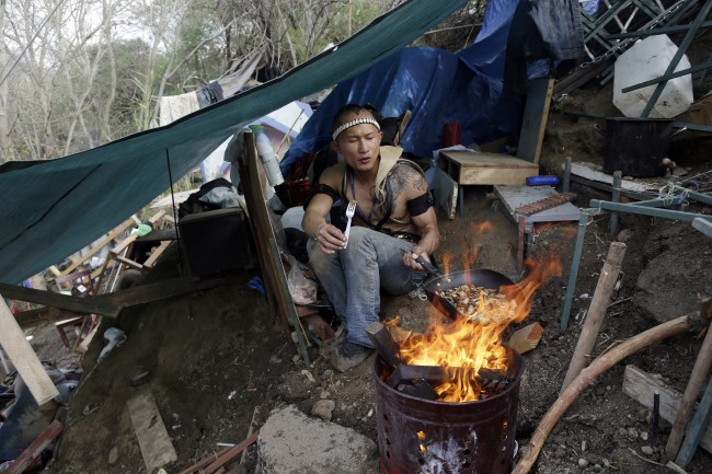 In this March 4, 2014 photo, a man who goes by the name of D cooks lunch from a makeshift tent where he lives in the Jungle, a homeless encampment in San Jose, Calif.