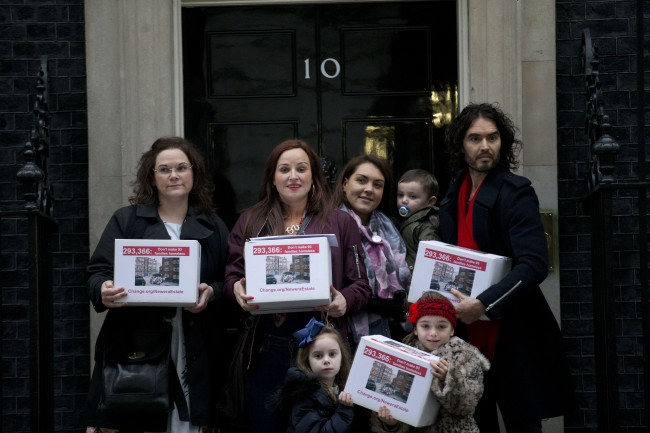 Residents from the New Era estate in east London, originally built as affordable housing for local workers, pose for photographs with their supporter British comedian Russell Brand, right, just before handing a petition into 10 Downing Street, Monday, Dec. 1, 2014.