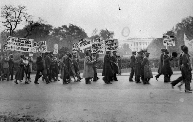 In this May 8, 1933 file photo, a long line of predominately African-American marchers parade past the White House in Washington to present a petition to President Roosevelt asking intervention to free the youths convicted in the Scottsboro, Ala., attack case. (AP Photo)