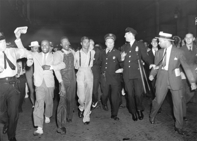 A throng at Penn Station greeted two of the five Scottsboro boys recently freed, upon arrival in New York July 26, 1937. Officers are shown escorting Olen Montgomery, center, wearing glasses, and Eugene Williams, wearing suspenders, through the crowd. (AP Photo) Ref #: PA.8658518  Date: 26/07/1937