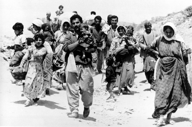 A Kurdish family walks down a mountain road near Shiranish carrying their few belongings to a refugee resettlement camp near Zakho in the allied security zone, May 9, 1991. Thousands of Iraqi Kurds were displaced from their homes in northern Iraq following failed rebellion against Saddam Hussein. (AP Photo/Heribert Proepper)
