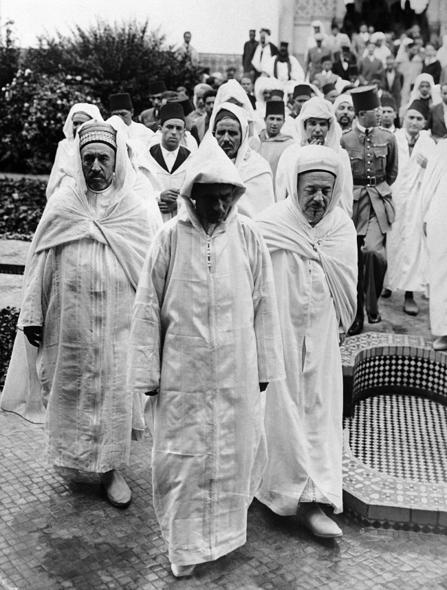 The Sultan of Morocco, Sidi Mohamed, who is on a visit to Paris, attended Friday ritual prayers at the mosque there, accompanied by believers from North Africa. The Sultan of Morocco, centre, leaving the Paris mosque with Si Saddour Ben Ghabri, right, Director of the Franco-Musulman Institute, on July 16, 1937. (AP Photo)