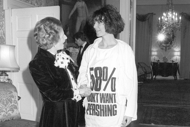 Prime Minister Margaret Thatcher greets fashion designer Katharine Hamnett, wearing at-shirt with a nuclear missile protest message, at 10 Downing Street, where she hosted a reception for British Fashion Week designers. Archive-1131406crop Ref #: PA.16297039
