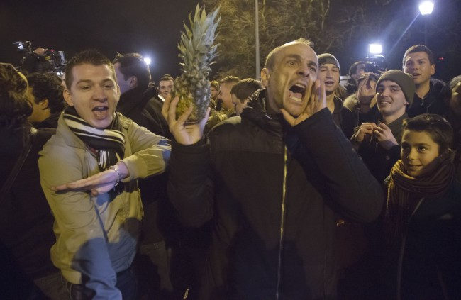 "People making the ""quenelle"" hand gesture, which French Interior Minister Manuel Valls has criticized as an ""inverted Nazi salute"" and holding a pineapple outside the Zenith arena where French comic Dieudonne's show was banned in Nantes, France, Thursday, Jan. 9, 2014. The French comic who is considered anti-Semitic was banned from performing Thursday night just hours after a court in Nantes said he could go ahead with his show. The comic was convicted last fall for using the word ""Shoananas,"" a mash-up of the Hebrew word for Holocaust and the French word for pineapple. (AP Photo/Michel Euler)"
