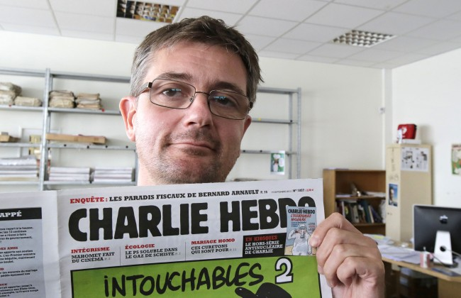 In this Sept.19, 2012 file photo, Charb , the publishing director of the satyric weekly Charlie Hebdo, displays the front page of the newspaper as he poses for photographers in Paris.