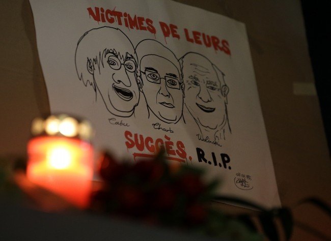 "A drawing depicting cartoonist Jean Cabut, left, Charlie Hebdo editor Stephane Charbonnier, center, and cartoonist Georges Wolinski, all three of whom were killed when masked gunmen stormed the Paris offices of a weekly newspaper Charlie Hebdo and reading in French, ""Victims of their success, R.I.P"", is placed outside the French Embassy as people gather to express solidarity with victims of the attack in Berlin, Germany,"