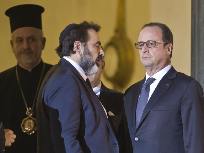 President of the French Jewish Consistory Joel Mergui, left, talks to French President Francois Hollande, right, as they walk out of the lobby of the Elysee Palace, after a meeting with religious leaders in Paris, Wednesday, Jan. 7, 2015.