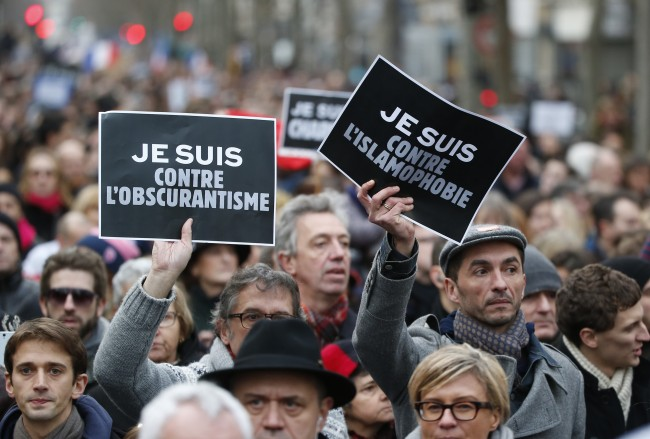 "Demonstrators hold posters reading ""I am against obscurantisme"", left, and ""I am against Islamophobia"" during a march in Paris, France, Sunday, Jan. 11, 2015. Thousands of people and world leaders converged on Paris in a rally of defiance and sorrow on Sunday to honor the 17 victims of three days of bloodshed that left France on alert for more violence. Obscurantisme is the act of making dark and deliberately obscuring facts from becoming known. (AP Photo/Michel Euler)"