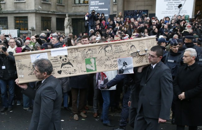 Pallbearers carry the casket of Charlie Hebdo cartoonist Bernard Verlhac, known as Tignous, decorated by friends and colleagues of the satirical newspaper Charlie Hebdo, at the city hall of Montreuil, on the outskirts of Paris, Thursday, Jan. 15, 2015