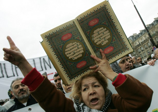 A Muslim women holds a copy of the Islamic holy book the Quran, whilst demonstrating among several thousand other Muslims, to protest against French newspapers that published cartoons of the Prophet Muhammad, in Paris, France, Saturday, Feb. 11, 2006. France's top national Muslim organization said it was launching legal action against the papers, with efforts likely focused on France Soir and Charlie-Hebdo. (AP Photo/Jacques Brinon)