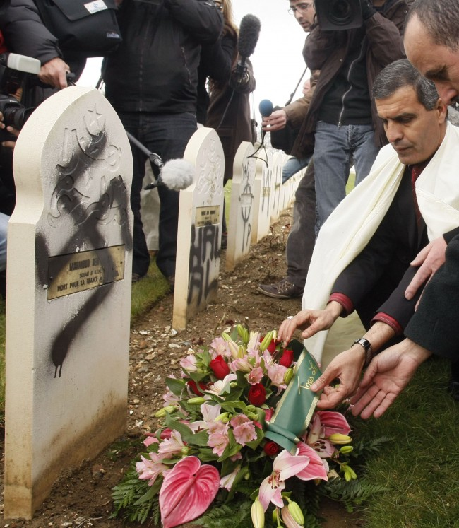 Abdelkader Aoussed, a representative of Paris mosque, lays a wreath of flowers at a defaced grave of Muslim World War I soldiers during a ceremony at the cemetery of Ablain-Saint-Nazaire, northern France, Monday April 7, 2008. Vandals inscribed Sunday night graves in the cemetery with anti-Islam slogans and also left graffiti singling out Justice Minister Rachida Dati, who is of North African origin. 148 tombs were targeted. (AP Photo/Michel Spingler)