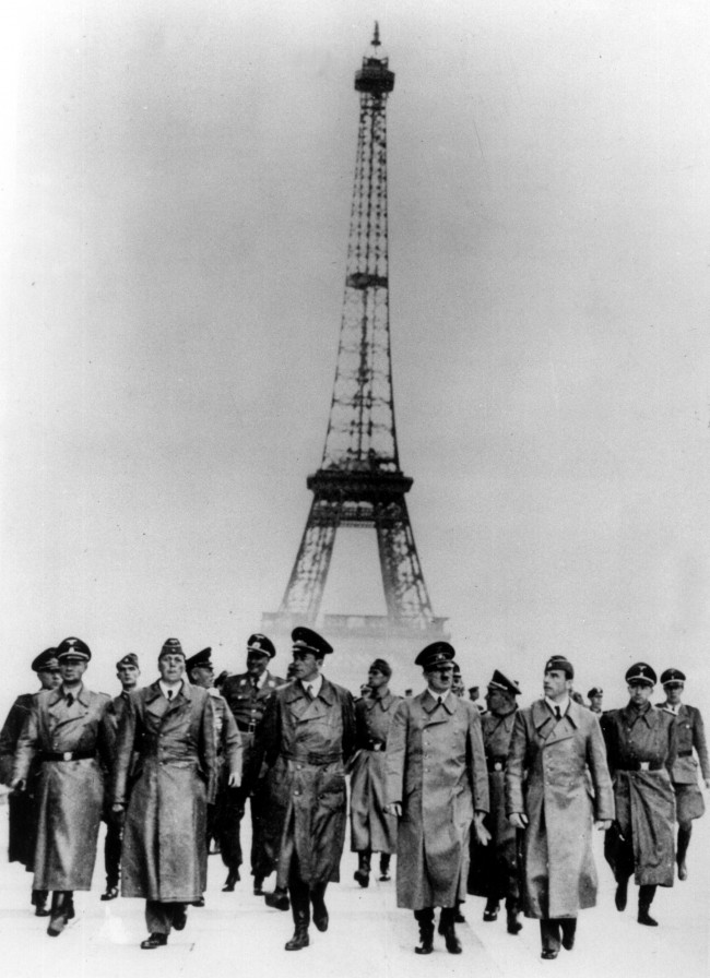 Nazi Party leader Adolf Hitler, front with mustache, is shown with other German officials walking in front of the Eiffel Tower in Paris, France in 1940. The others are not identified. (AP Photo)