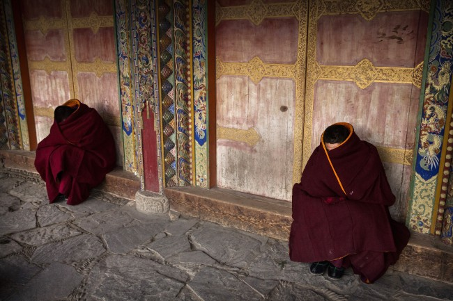 Tibetan Buddhist Monks of the Gelug, or Yellow Hat order, rest on a cold morning outside prayers during Monlam or the Great Prayer rituals on March 3, 2015 at the Labrang Monastery, Xiahe County, Amdo, Tibetan Autonomous Prefecture, Gansu Province, China. Labrang Monastery is one of the six great monasteries of the Gelug school of Tibetan Buddhism and one of the largest outside of the Tibetan Autonomous Region. Monlam, the most important prayer event for many Tibetans was banned during the Cultural Revolution in China but once again in recent years it is celebrated in many areas. (Photo by Kevin Frayer/Getty Images)
