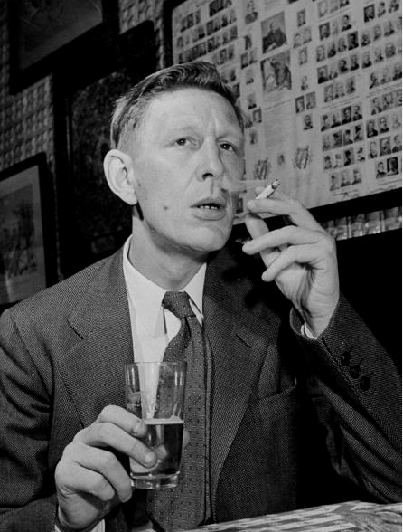 American (English-born) poet W.H. (Wystan Hugh) Auden holding glass & smoking cigarette in undated, serious cafe portrait.