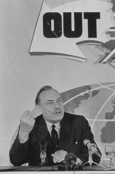 4th June 1975: Ulster Unionist politician and scholar Enoch Powell making a speech under a large arrow reading 'Out' beside a map of Britain.
