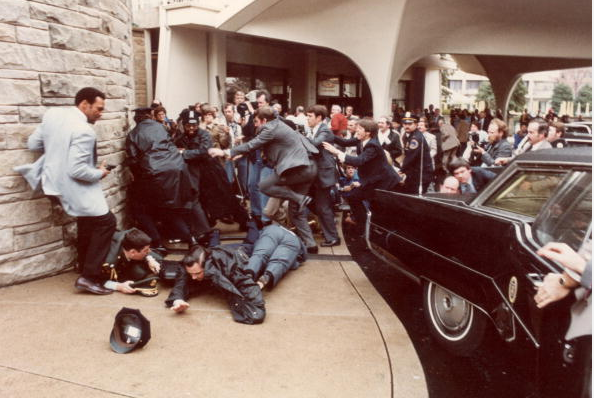 Police and Secret Service agents diving to protect American President Ronald Reagan amid a panicked crowd during an assassination attempt by John Hinckley Junior outside the Washington Hilton Hotel, Washington, DC.