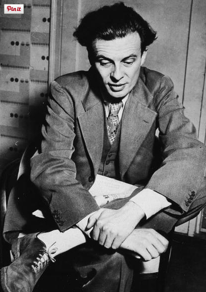 British writer Aldous Huxley (1894 - 1963) sits with a newspaper on his lap, 1930s.