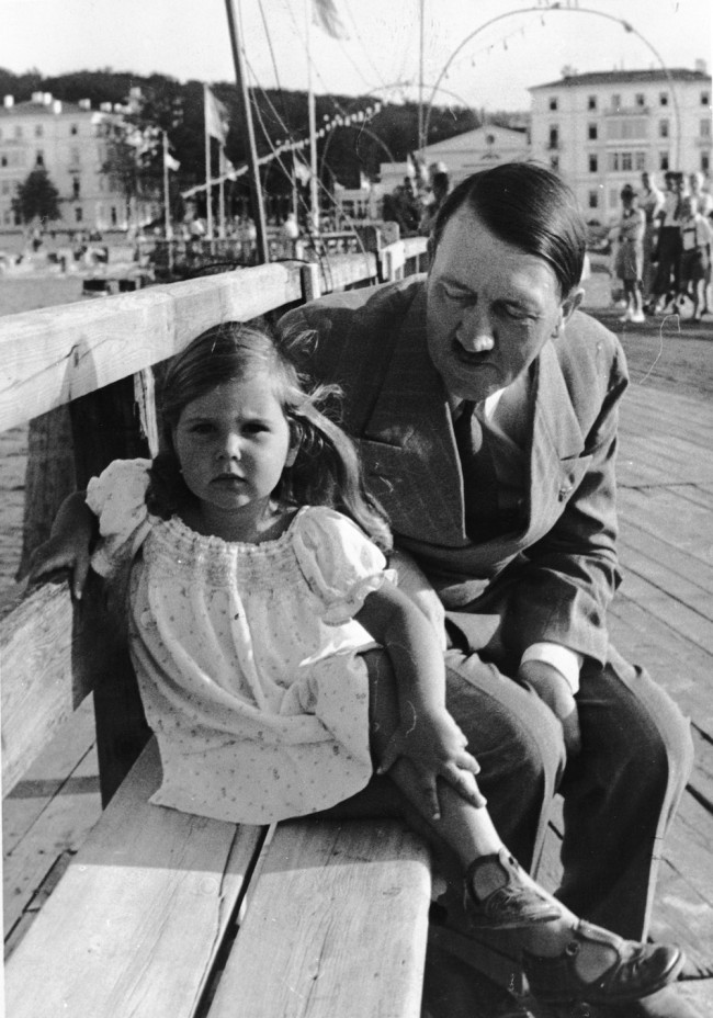 circa 1935:  German dictator Adolf Hitler sitting on a bench with Helga Goebbels, daughter of Nazi propagandist Paul Joseph Goebbels.  (Photo by Fox Photos/Getty Images)