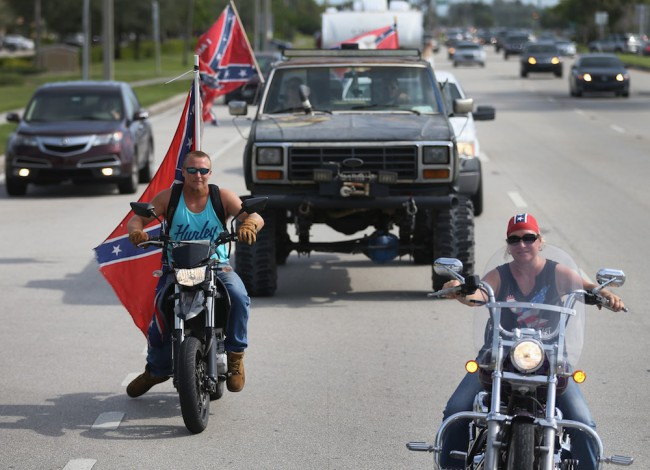 LOXAHATCHEE, FL - JULY 11:  Austin Powell (L) and Tracy Casey participate in a rally to show support for the American and Confederate flags on July 11, 2015 in Loxahatchee, Florida. Organizers of the rally said that after the Confederate flag was removed from South Carolinas State House it reinforced their need to show support for the Confederate flag which some feel is under attack.  (Photo by Joe Raedle/Getty Images)