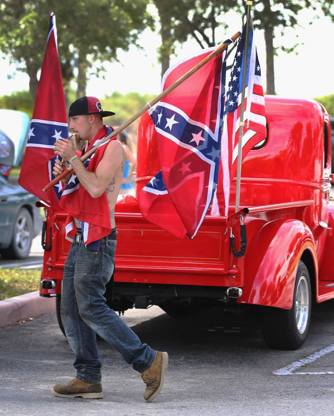 LOXAHATCHEE, FL - JULY 11: A person who didn't want to give his name displays a Confederate flag as he joins in a rally to show support for the American and Confederate flags on July 11, 2015 in Loxahatchee, Florida. Organizers of the rally said that after the Confederate flag was removed from South Carolinas State House it reinforced their need to show support for the Confederate flag which some feel is under attack.  (Photo by Joe Raedle/Getty Images)