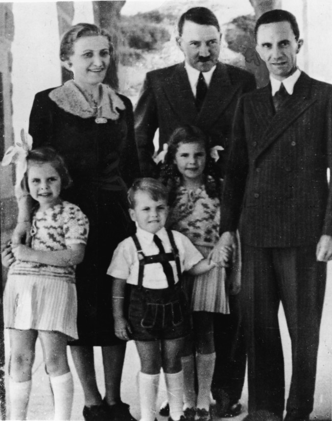 Genocidal German dictator and Nazi leader Adolf Hitler (1889 - 1945) (rear center) stands with Nazi Propaganda Minister Joseph Goebbels (1897 - 1945), his wife Magda (1901 - 1945), and their three oldest children, left to right, Hilda (1934 - 1945), Helmut (1935 - 1945), and Helga (1932 - 1945), late 1930s. (Photo by Express Newspapers/Getty Images)