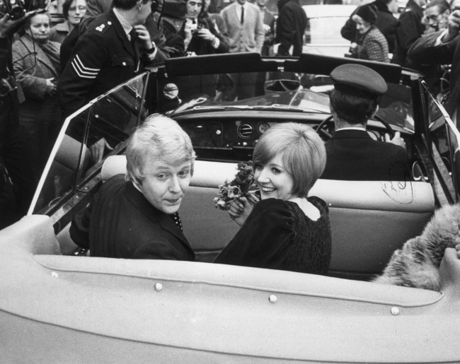 25th January 1969:  Pop singer and TV star Cilla Black and her husband and manager Bobby Willis, give a backward glance as they leave Marylebone register office in a car after their wedding.  (Photo by Michael Webb/Keystone/Getty Images)