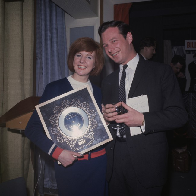 1964:  Pop singer Cilla Black with managerand promoter Brian Epstein (1934 - 1967). She is holding the Silver Disc for her record, 'Anyone who had a Heart'  (Photo by Hulton Archive/Getty Images)