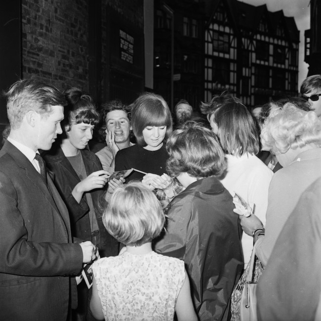 17th August 1964:  Liverpudlian singer and television personality Cilla Black signing autographs for fans outside the London Palladium.  (Photo by Larry Ellis/Express/Getty Images)