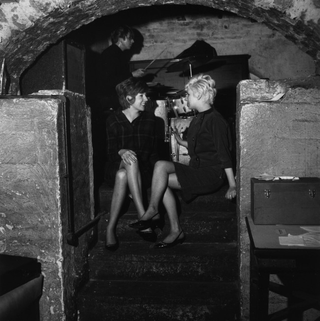 24th April 1963:  Pop singer Cilla Black (left) talking to a friend at the Liverpool music venue The Cavern, where The Beatles had a residency early in their career.  (Photo by John Pratt/Keystone Features/Getty Images)