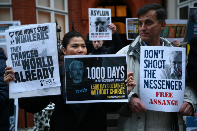 LONDON, ENGLAND - MARCH 16: Supporters hold placards during a vigil outside the Ecuadorean embassy on March 16, 2015 in London, England. Wikileaks founder Julian Assange has lived there since claiming refuge in 2012 to avoid extradition to Sweden where he is wanted for questioning over sex assault allegations. Supporters are to hold a vigil today to mark the 1,000 days since Assange originally claimed asylum at the embassy.  (Photo by Carl Court/Getty Images)