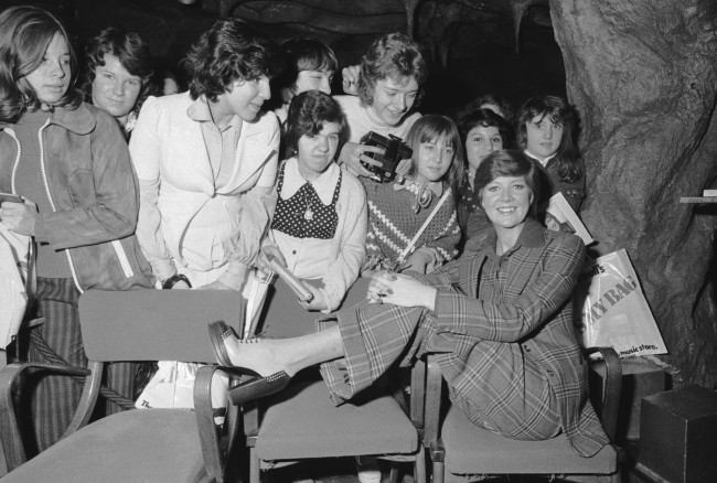 Singer and TV presenter Cilla Black poses with a group of fans, 22nd October 1973. She is wearing a suit in a checked pattern by Tommy Nutter. (Photo by Tim Graham/EveningStandard/Hulton Archive/Getty Images)