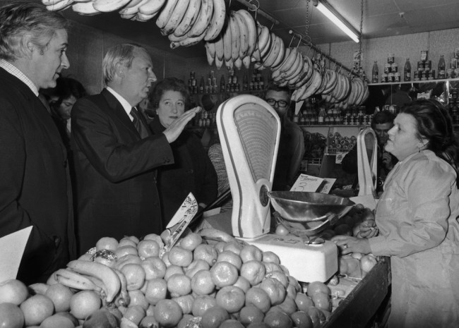 British Prime Minister Edward Heath (1916 - 2005) talks to shop assistant Sheila Kane in a greengrocer's shop on Mill Hill Broadway, London, during an electioneering tour, 19th February 1974. Kane expressed concerns about high prices and extreme cold in the shop due to the three-day working week.  (Photo by Dennis Oulds/Hulton Archive/Getty Images)