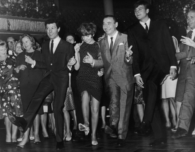 Big Bandleader Joe Loss (1909 - 1990) introduces Lionel Blair's new dance 'The Kick' at the Cafe de Paris, London, 29th September 1965. Doing the kick, from left to right, are Blair, Cilla Black, Joe Loss and Billy J. Kramer. (Photo by Douglas Miller/Keystone/Getty Images)