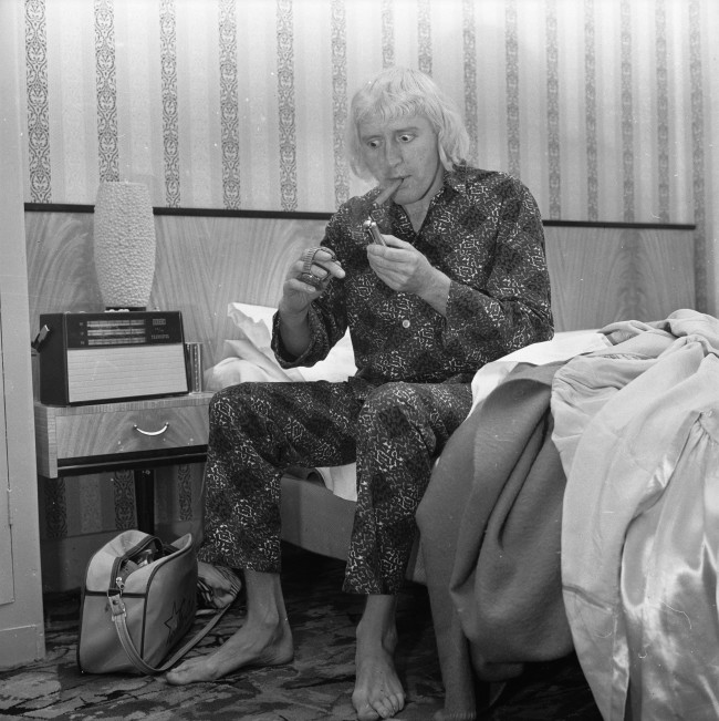 4th February 1965:  Disc-jockey, Jimmy Savile lights his breakfast cigar in the Bloomsbury hotel room which he has made his home.  (Photo by Chris Ware/Keystone Features/Getty Images)