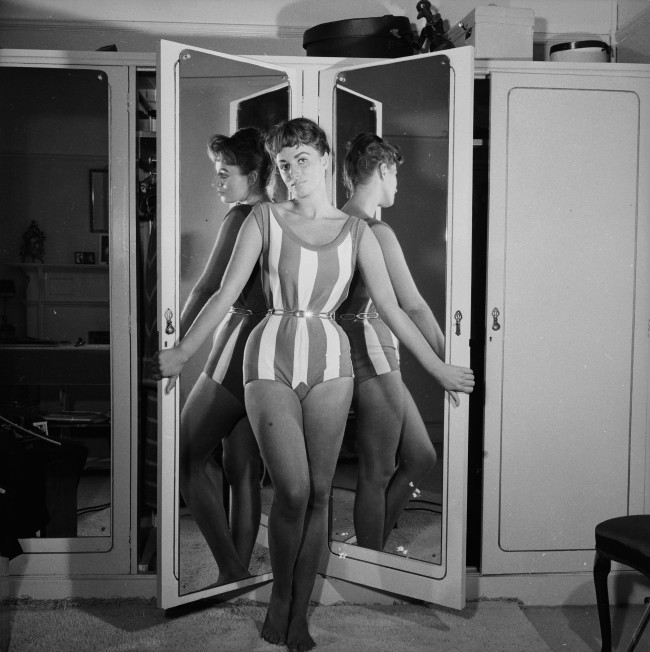 October 1956:  Actress Jackie Collins reflected in her wardrobe mirrors while posing in her London flat.  (Photo by John Pratt/Keystone Features/Getty Images)