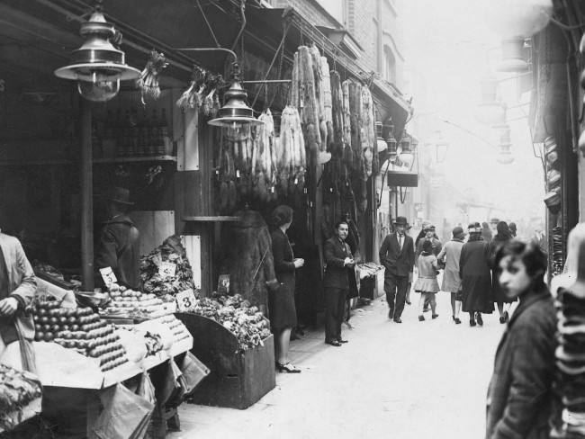 circa 1930:  Berwick street market in Soho, London, with stalls selling fruit and vegetables and fur coats and stoles.  (Photo by Fox Photos/Getty Images)