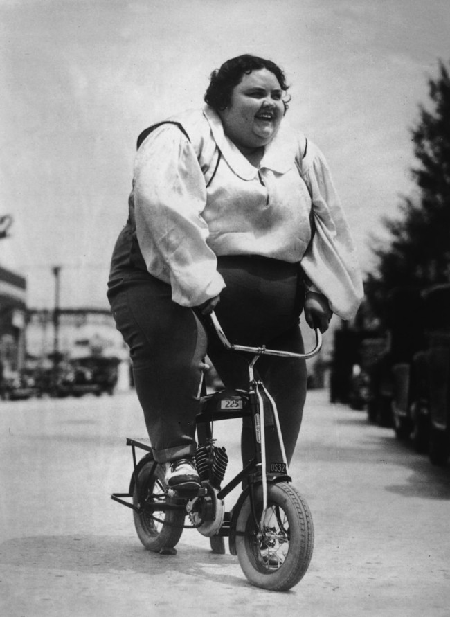 circa 1935:  A rather large woman riding a mini-autobike.Tiny Griffin preparing to take part in a South California Bicycle Parade at Ocean Park.  (Photo by General Photographic Agency/Getty Images)