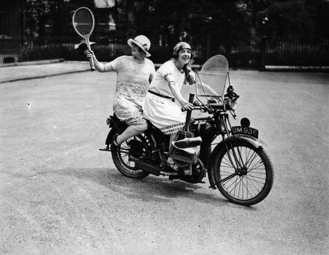 1925:  Two women set off on a BSA motorbike to play tennis after work.  (Photo by Topical Press Agency/Getty Images)