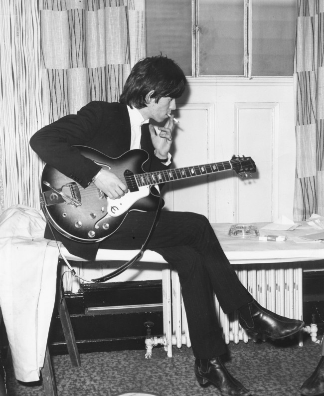 Portrait of 'The Rolling Stones' musician Keith Richards playing his guitar and smoking a cigarette, 1964. (Photo by Cyrus Andrews/Keystone/Getty Images)