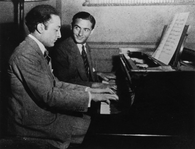 circa 1925: Russian-born US composer Irving Berlin (Israel Baline, 1888 - 1989) at the keyboard with violinist Jascha Heifetz. (Photo by Henry Guttmann/Getty Images)